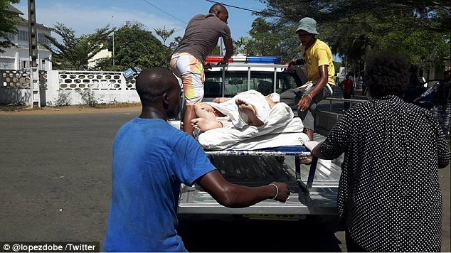Locals help a badly injured victim on to the back of a backup truck following the sudden terror attack