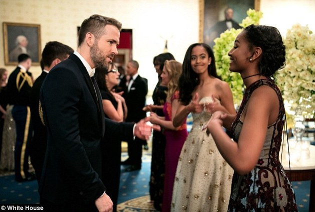 Malia Obama appears in the background of this picture, seemingly giving her sister a sarcastic thumbs-up as Sasha meets Canadian actor Ryan Reynolds at a state dinner on Thursday
