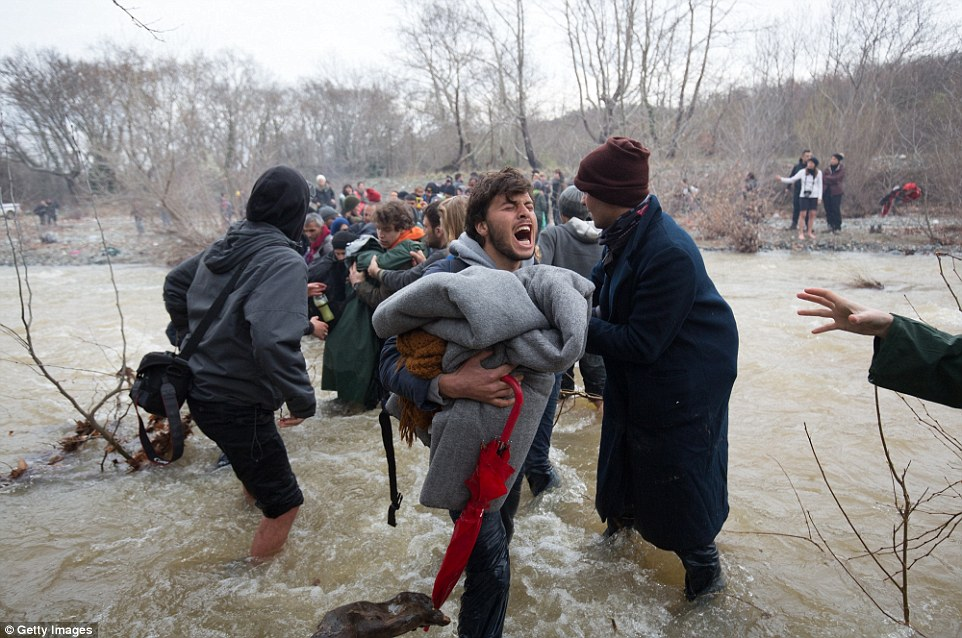 La decisión de Macedonia a cerrar sus fronteras a los inmigrantes ha dejado a muchos en busca de rutas alternativas a la tierra prometida del norte de Europa. En la foto, un hombre, es de suponer que grita en relieve, llega al otro lado del río, mientras que agarra a sus pertenencias
