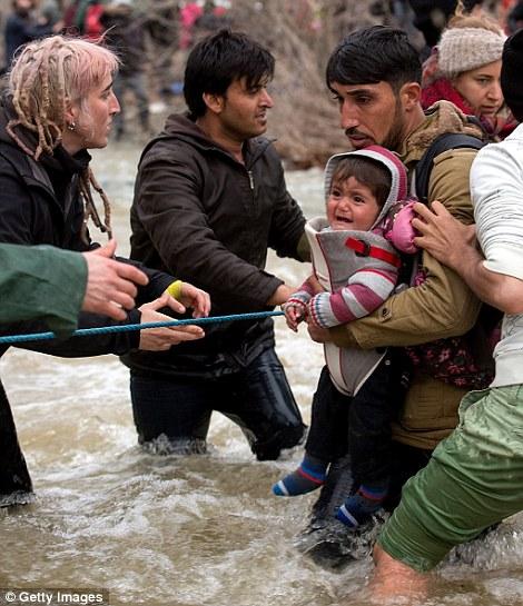 En la foto, un padre migrante se aferra a una cuerda guía cuando cruza el río con su hija recién nacida