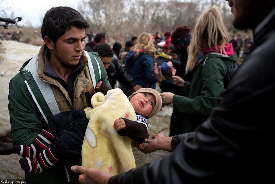 En la foto, un migrante tiene un bebé envuelto contra el frío como extensiones de los demás cruzan el río con sus pertenencias y seres queridos