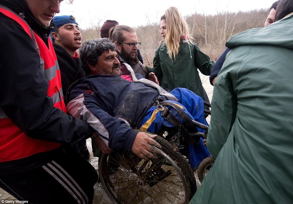 Nadie se queda atrás en la lucha por una vida mejor como un grupo de migrantes voluntarios y levantar a un hombre en una silla de ruedas a través del agua helada
