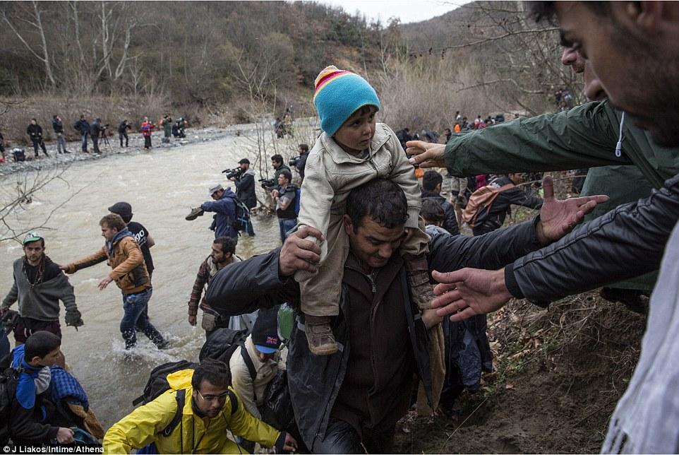 A medida que los migrantes tirarse hacia fuera del agua y la lucha por una orilla fangosa que se les ofrece ayuda por otros que han cruzado delante de ellos