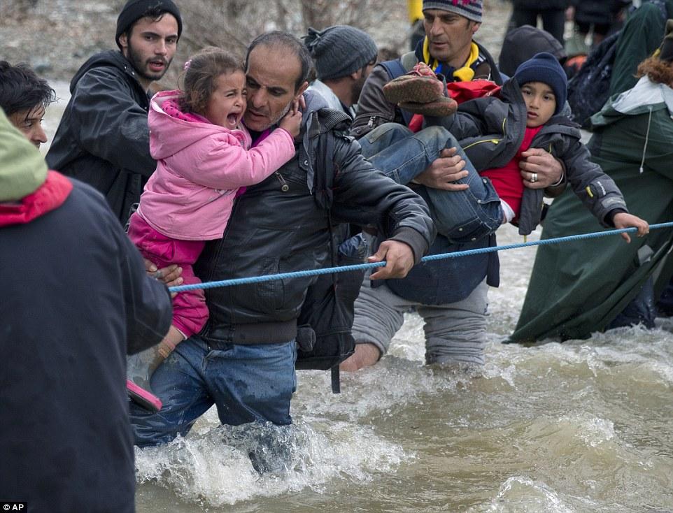 Un niño llora como migrantes cruzan un río al intentar llegar a Macedonia en una ruta que evite la valla fronteriza