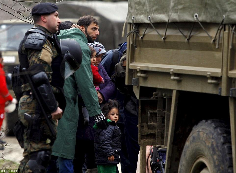 soldados macedonios acompañan a los migrantes que han cruzado la frontera ilegalmente desde Grecia en camiones del ejército en el pueblo de Moini