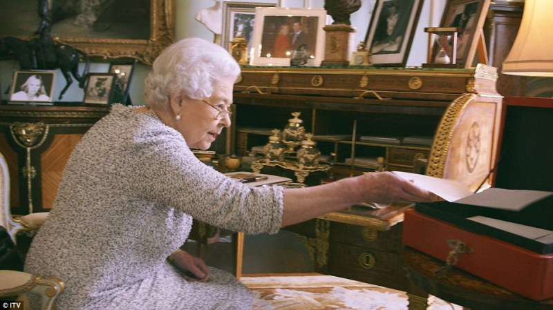 Her Majesty The Queen at work in Buckingham Palace reading daily correspondence from her 'red box' of official papers
