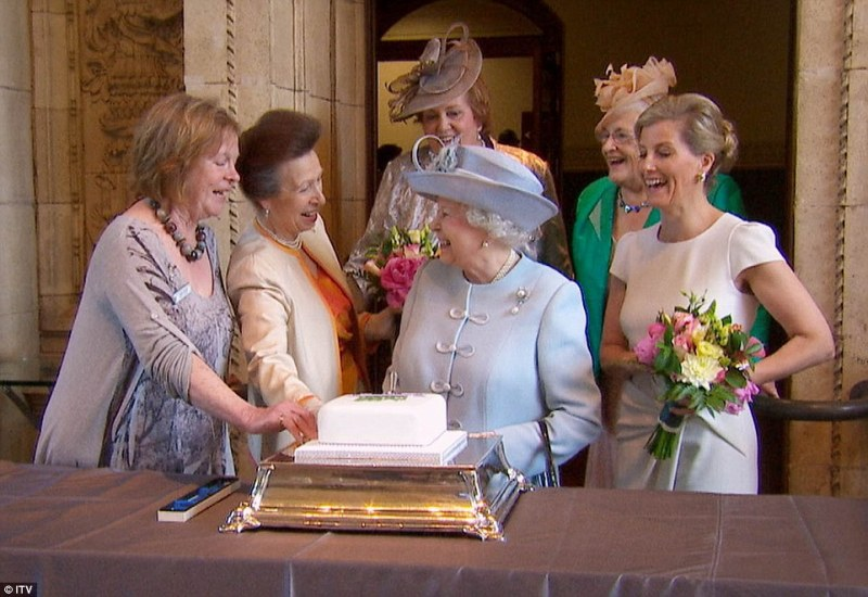 The Queen attends the 100th Annual General Meeting of the Women's Institute at the Royal Albert Hall and cuts a centenary fruit cake with Julie Clarke, chairwoman of the WI's North Yorkshire West Federation, the Princess Royal and the Countess of Wessex (right)