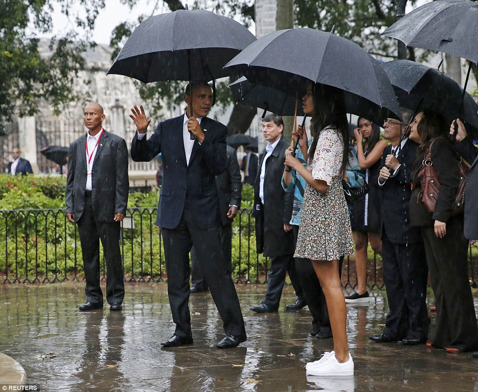 The tour must go on! The president appeared to be explaining something to his daughter Malia as they were guided around Old Havana on a rainy evening