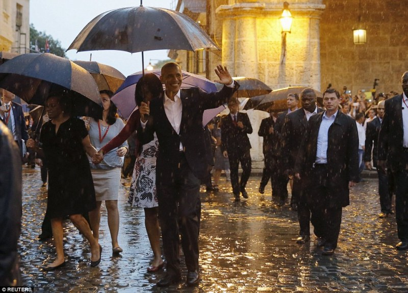 President Barack Obama waved to hundreds of Cubans gathered in Old Havana as he was taken on a tour amid heavy rain