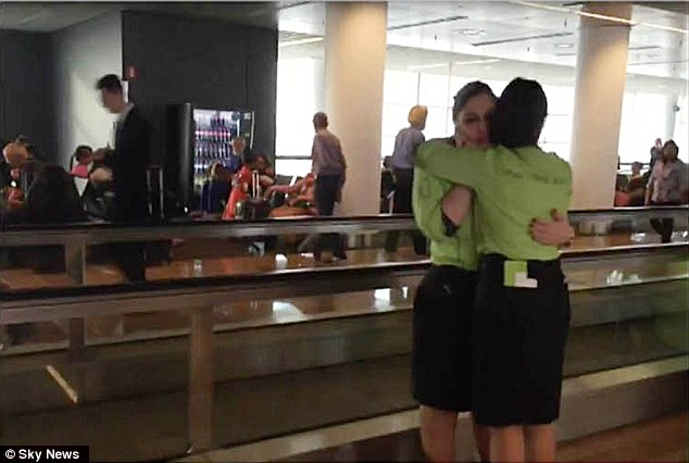 Comfort: Two airport workers embrace in the aftermath of the attacks in Brussels this morning