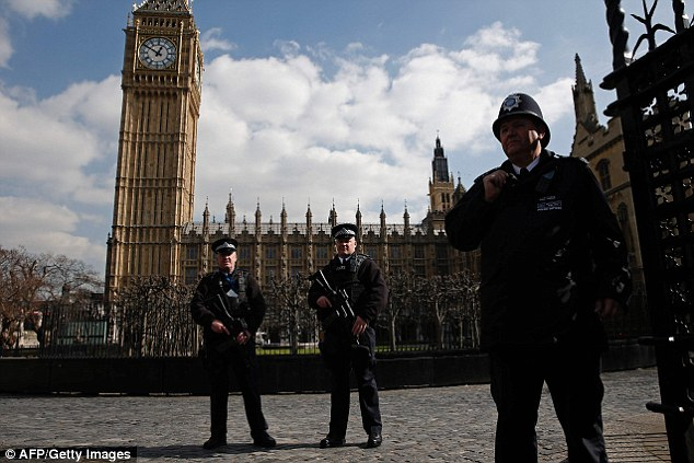 Armed British police officers stand on duty outside the entrance to the Houses of Parliament in London today