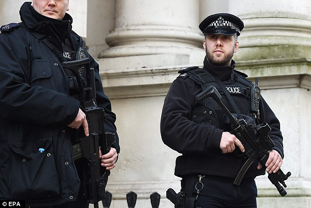Armed police officers in central London after the terrorist attacks in Brussels earlier today