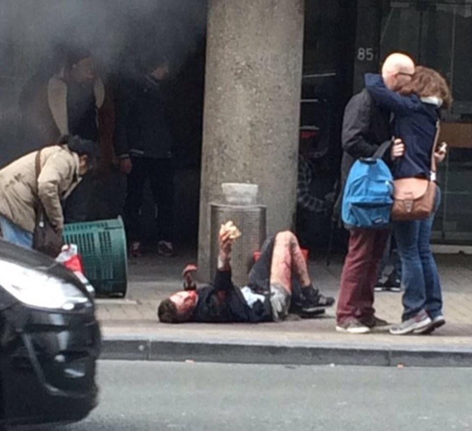 Consecuencias: Un hombre se encuentra afectada en el pavimento como sobrevivientes se besan en el alivio después de sobrevivir a los bombardeos, que ha matado a por lo menos diez