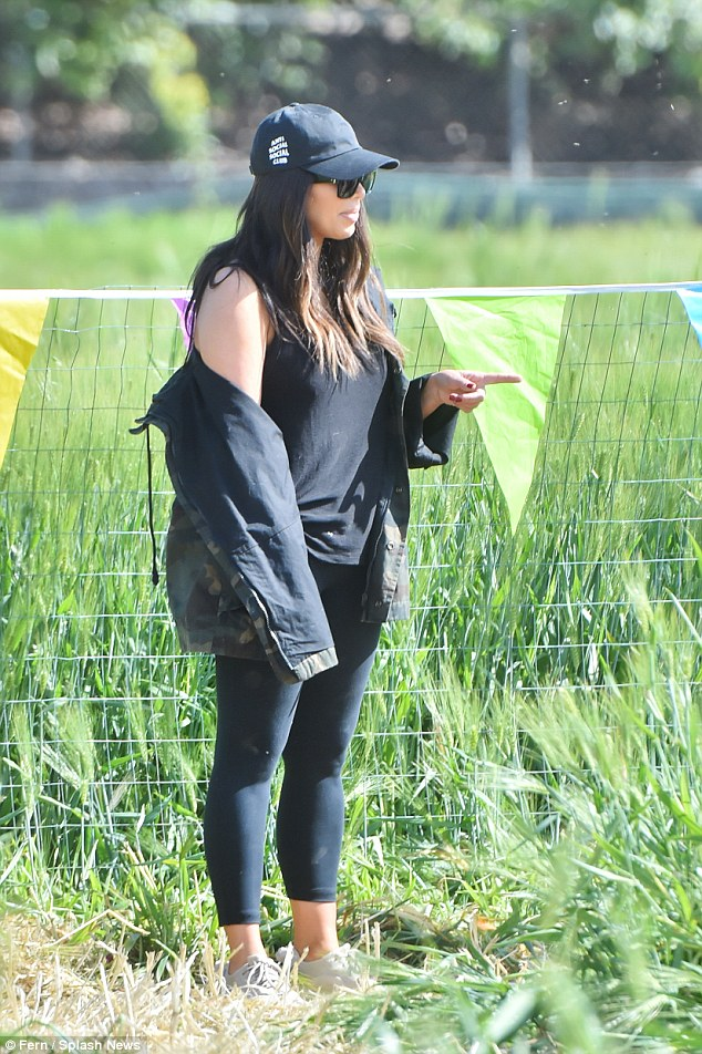 No Easter dress: Kim opted instead for a black leggings and top combo, covering up in a camouflage jacket