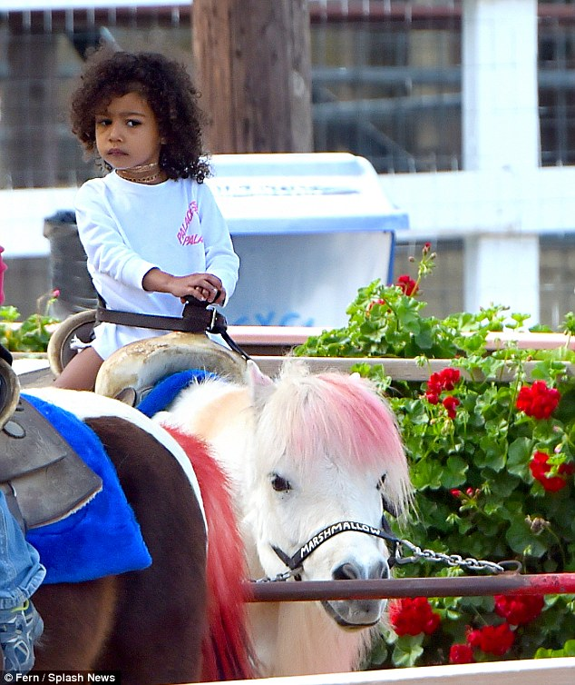 Little rider: North held on tight as her pink-haired pony Marshmallow walked the circuit