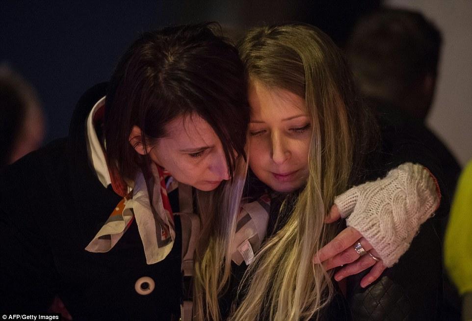 Buscando la comodidad de una u otra: Dos mujeres se abrazaron fuera del aeropuerto de Bruselas, ya que asistieron a una vigilia en el duelo de los que murieron