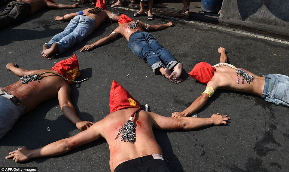 Roman Catholics prostrate in front of a chapel while still bearing the wounds caused by a bloody flagellation ceremony in Manila