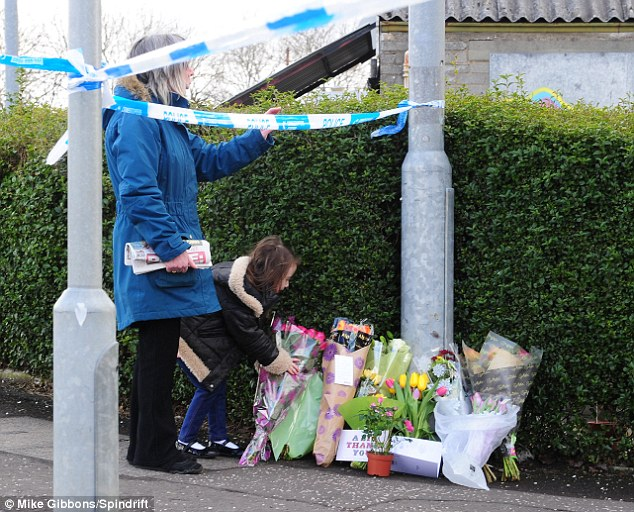 Flowers were placed at the scene. A neighbour said: 'He was the most peace-loving man you could meet'