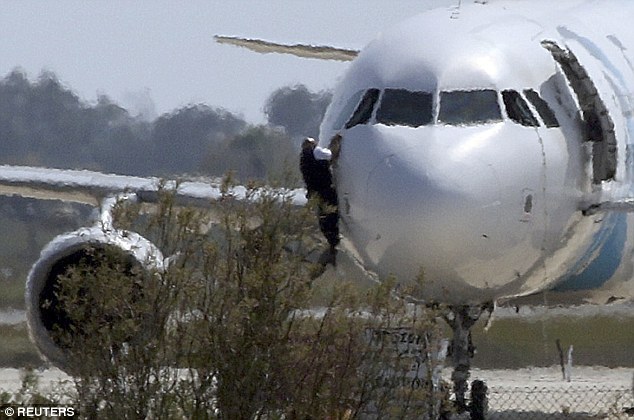 Cyprus police have evacuated a stretch of beach near the tarmac, as at least four more people were allowed to leave the plane shortly after midday, with one man seen climbing out of the cockpit