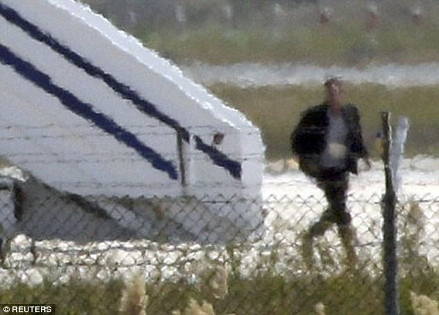 A man thought to be Seif Eldin Mustafa leaves the hijacked Egyptair Airbus A320 at Larnaca Airport, after which he raised his hands in the air and 'threw some items on the ground'
