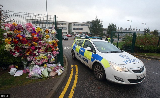 A police car passes floral tributes outside Cults Academy in Aberdeen shortly after a fight ended in the death of Bailey