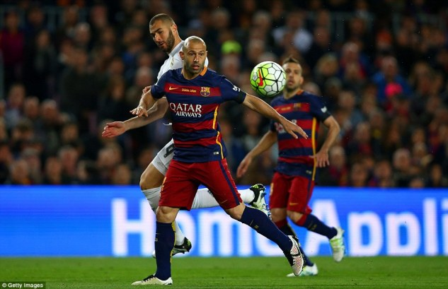 Barca defender Mascherano holds off the challenge of Real forward Karim Benzema