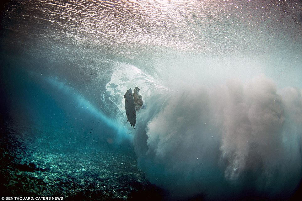 The photographerlooks up on surfers as they paddle out and ride waves on the water's surface