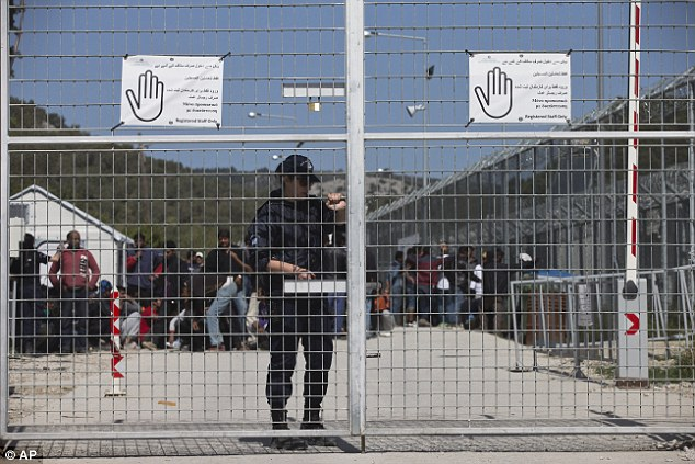 A Police officer closes the gate of Moria camp as refugees behind her protest against the EU- Turkey deal