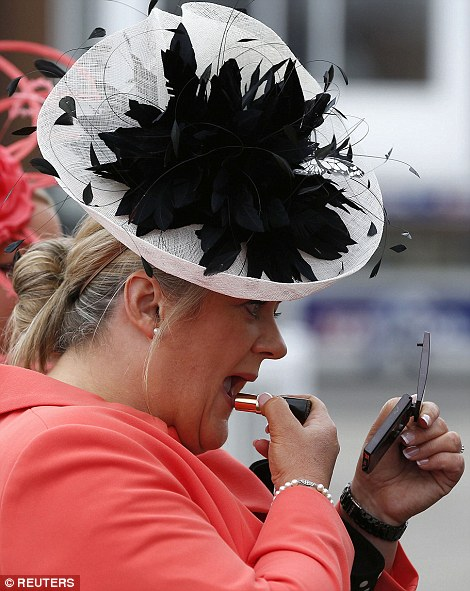 A woman touches up her lipstick as she prepares for a day of racing action