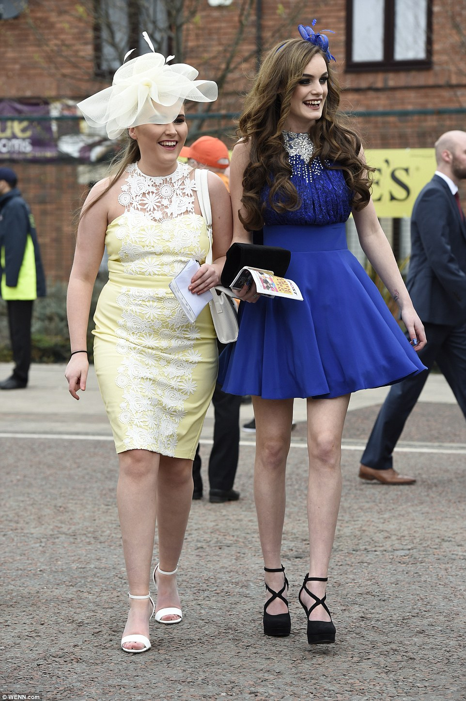 A woman in a yellow dress with a white lace panel arrived with a friend in a royal blue dress with diamante embellishment