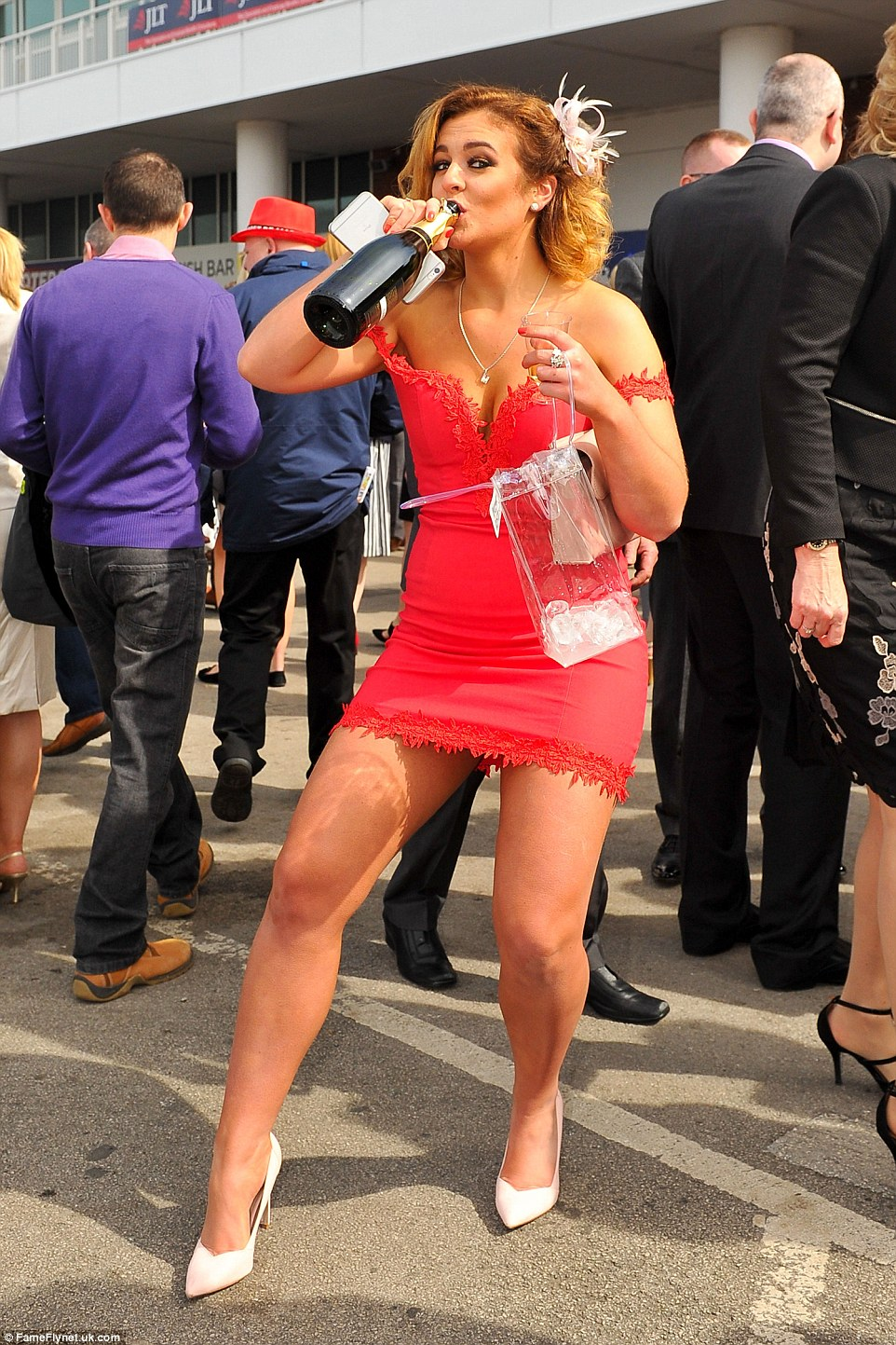 A partygoer necked champagne straight from the bottle as she soaked up the atmosphere at Ladies Day