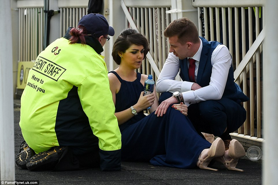 A woman was seen sitting down talking to a member of event staff while a male companion looked on, concerned