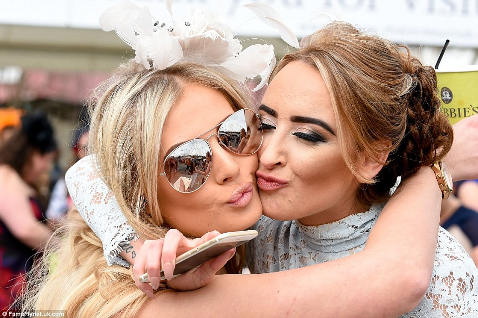 Two friends pucker up for a playful smooch at the end of a fun day at Aintree