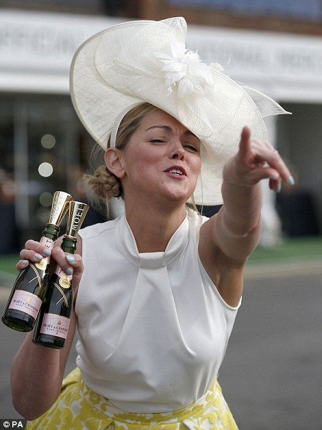 A female racegoer with two mini bottles of champagne