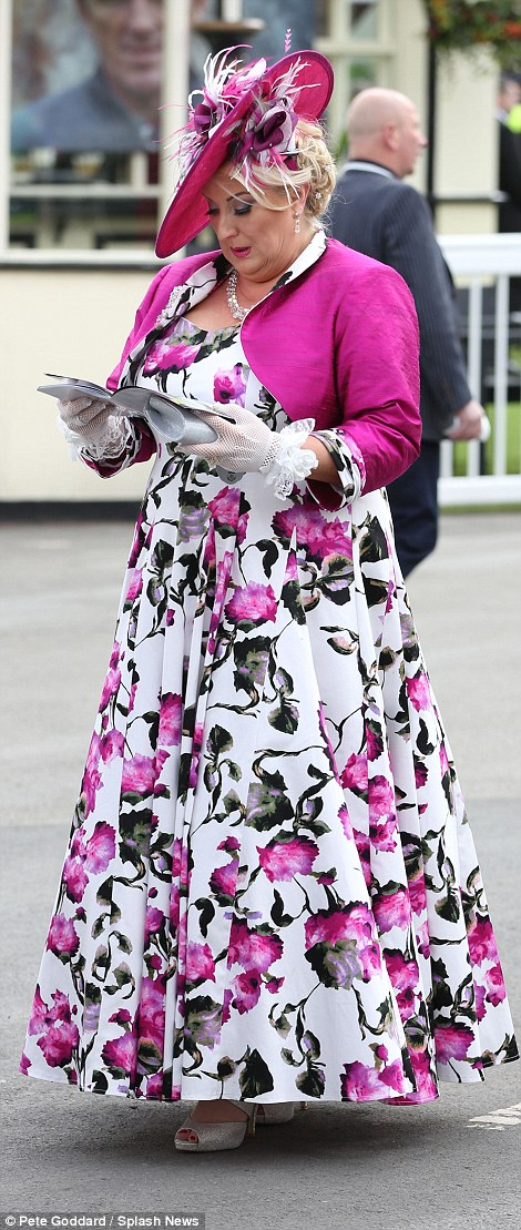 A colourfully dressed woman studies the programme on arrival at the course