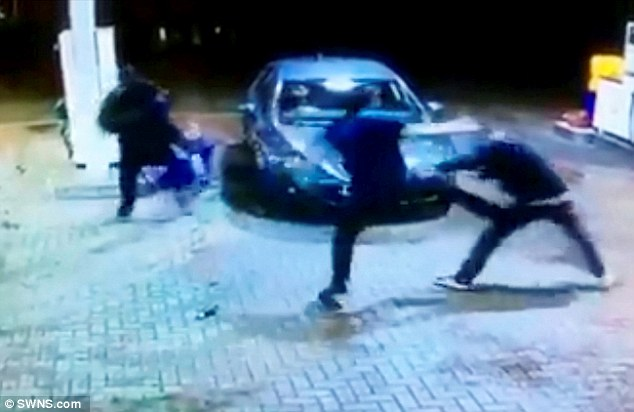Brawl: After stumbling against the car, which is driven away, the victim is seen falling over where he is again kicked and punched repeatedly by two men while he holds his hands up begging them to stop