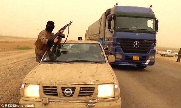 Um lutador ISIS equipa um posto de controle da estrada, na província de Anbar, no qual os veículos são parados e revistados por funcionários do governo iraquiano e oficiais militares