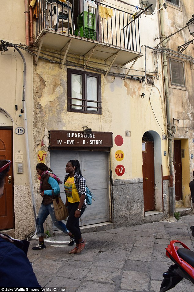 Closed: In March, a brothel (pictured above the electrics shop) run by a Nigerian gang in Ballaró was raided and closed down by police. The women in the picture are not prostitutes