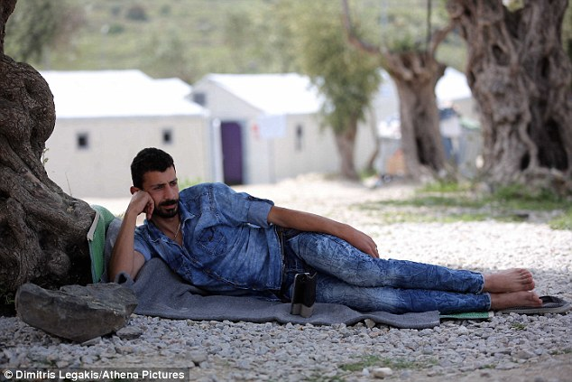 Frustration: For many, the disappointment of getting so far, only to get stuck once more has been hard to deal with. Pictured: A Syrian man listens to music at the camp