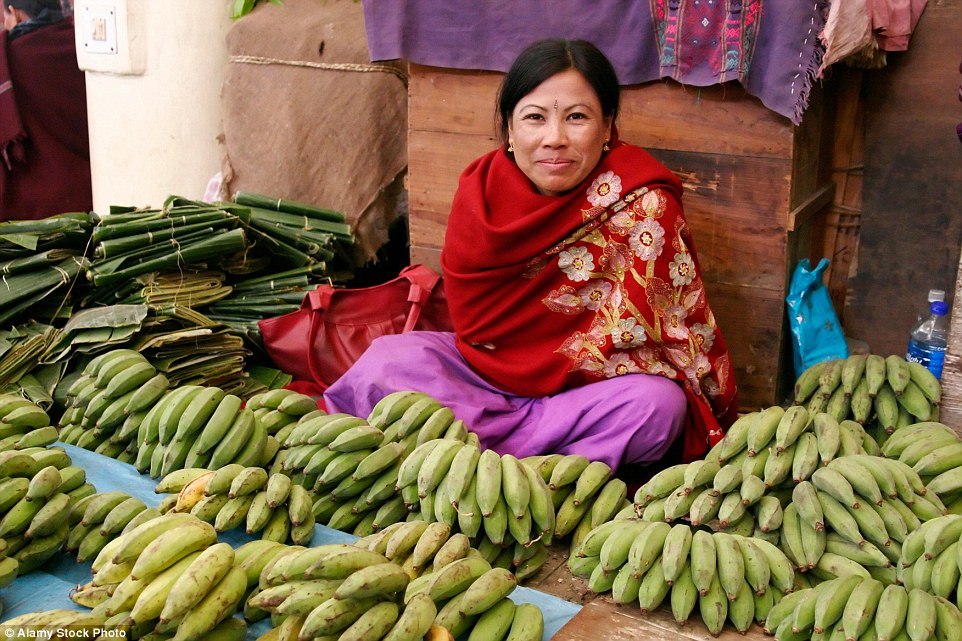Dating back 500 years, Ima Keithel which translates as 'mother's market' is a meeting ground and trading hub. A woman sells bananas (pictured)