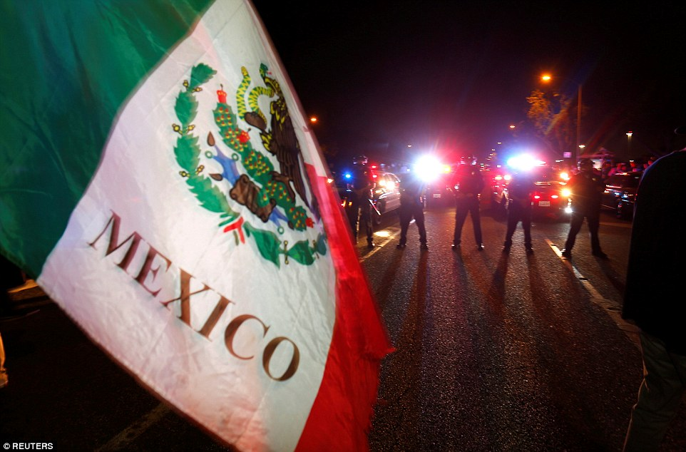 Police in riot gear form a line to break up a group of protesters, one with a Mexican flag, outside Trump's campaign rally