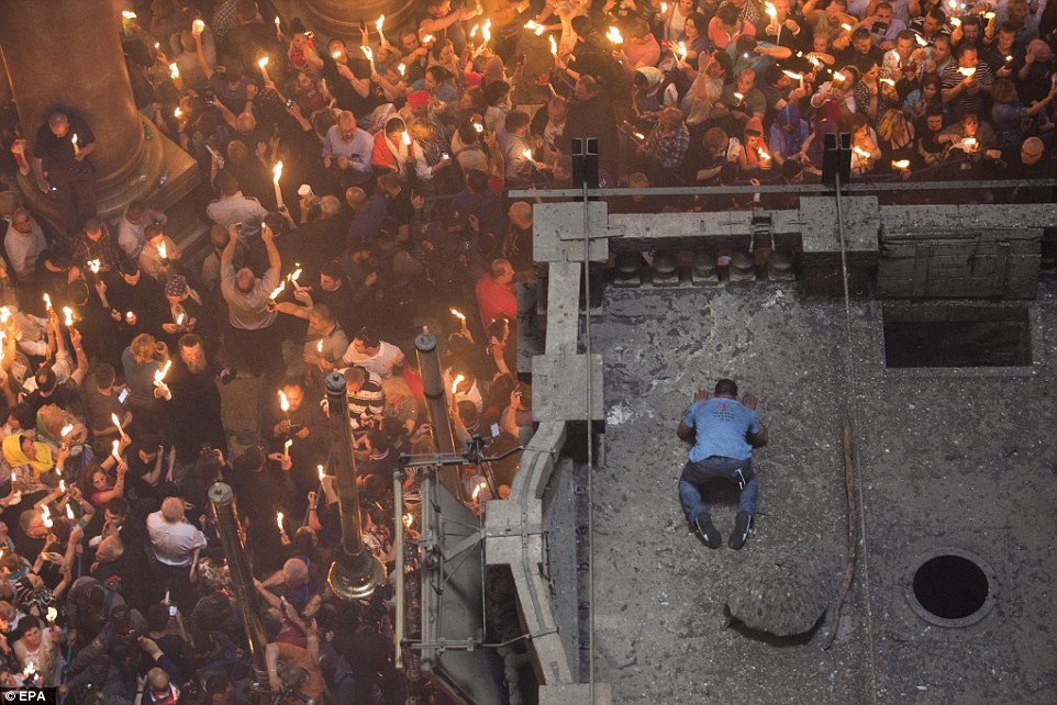 An Orthodox Christian worshipper on the roof of the Tomb of Christ as the miracle of the Holy Fire occurs in the Church of the Holy Sepulchre, Jerusalem, Israel