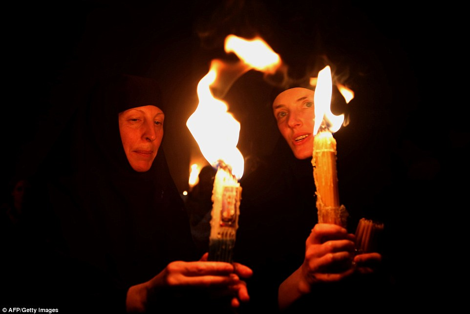 "Russian Orthodox nuns hold candles lit from the ""Holy Fire"" as thousands gather in the Church of the Holy Sepulchre in Jerusalem"