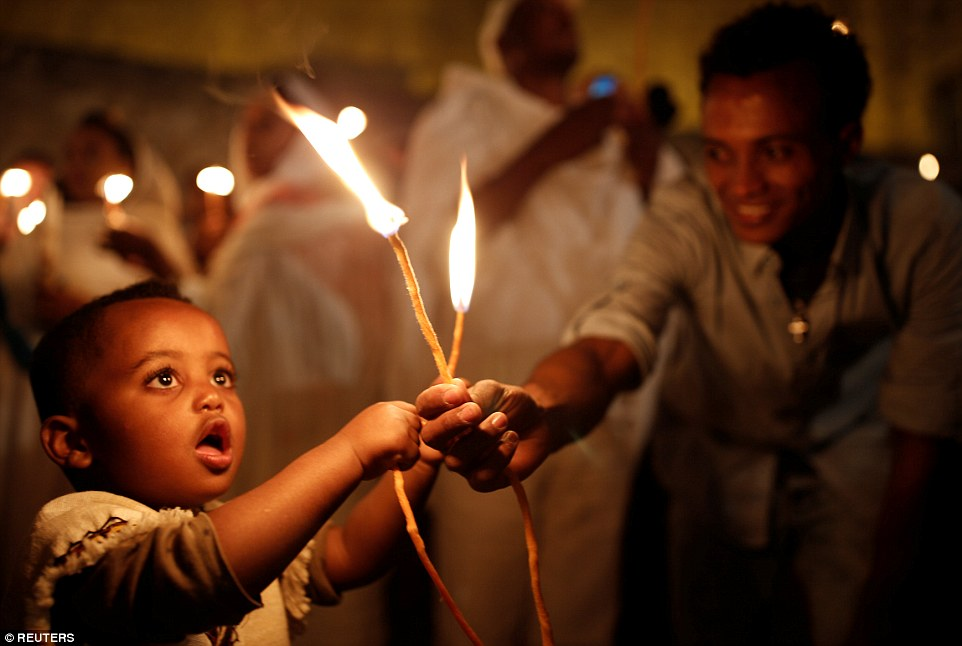 An Ethiopian boy holds candles during the Holy Fire ceremony at the Ethiopian section of the Church of the Holy Sepulchre in Jerusalem