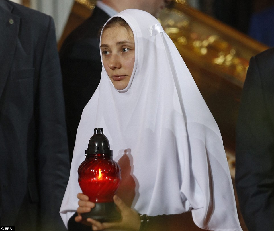 A Russian nun holds a candle with the Holy Fire from Jerusalem as she takes part in the Orthodox Easter holiday service in Moscow's Christ the Savior Cathedral, Russia
