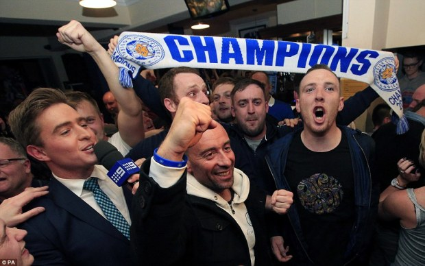 Leicester City fans celebrate in the Market Tavern in Leicester after seeing their side crowned Barclays Premier League champions following Tottenham Hotspur's 2-2 drew against Chelsea.