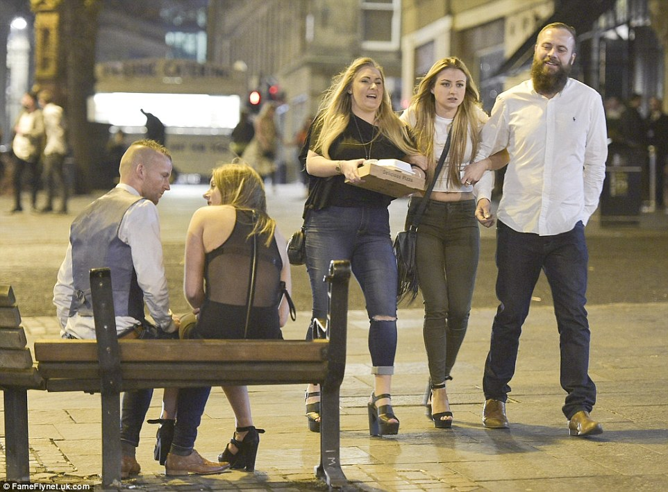 Three friends make their way home with a pizza (right) while a couple sit for a chat on a nearby bench after a boozy Bank Holiday weekend