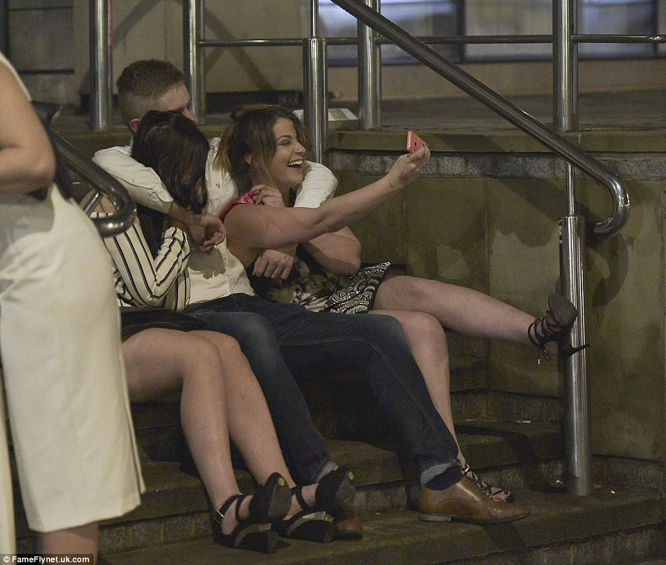 Three friends take a selfie to capture their night while sat on some outside steps as the Bank Holiday weekend comes to an end