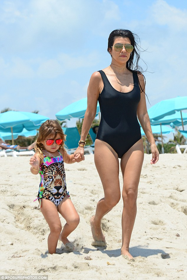 Hopping to the sea: Kourtney looked absolutely stunning in her swimsuit as she took three-year-old daughter Penelope for a dip in the aqua-blue sea
