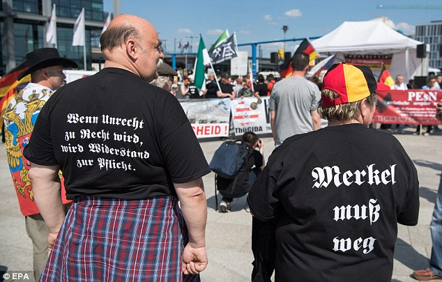 Protesters wear t-shirtswritten with the messages 'When wrong becomes right, resistance becomes obligatory' and 'Merkel must go'
